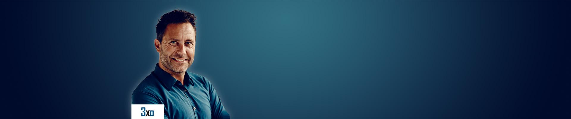Mand står foran blå gradueret baggrund med logo